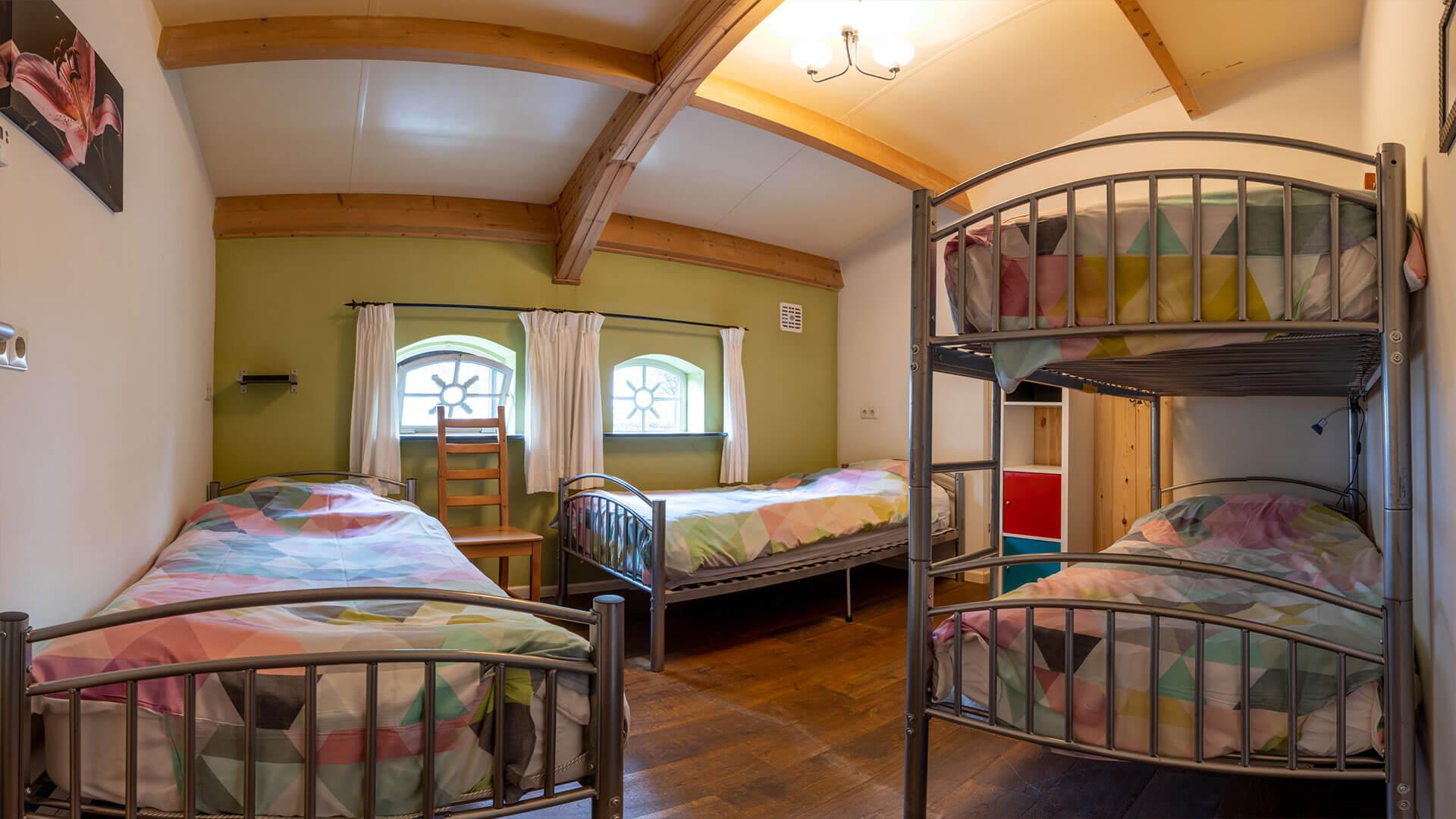 grote slaapkamer met 2 bedden en stapelbed